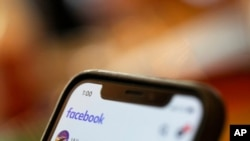 FILE - A smartphone displays a Facebook page in an illustration photo taken Aug. 11, 2019.