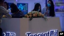 Visitantes a la Feria Internacional China de Comercio de Servicios (CIFTIS) reunidos alrededor de un stand de la firma de tecnología china Tencent el 5 de septiembre de 2020 en Beijing.