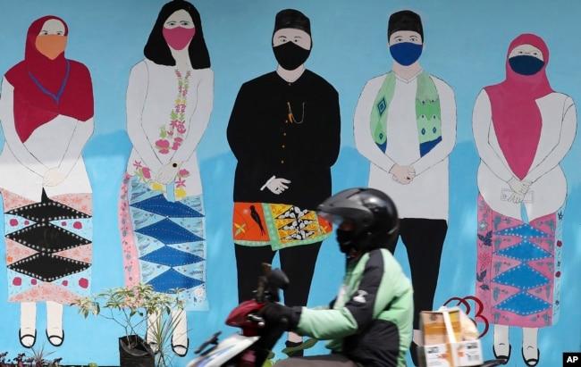 Seorang pria mengendarai sepeda motor melewati mural bertema virus corona di Jakarta, Selasa, 22 Juni 2021. (AP)