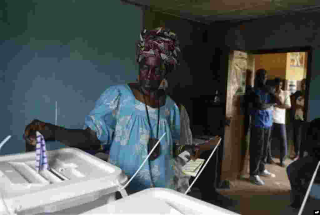 ຜູ້ຍິງຄົນນຶ່ງປ່ອນບັດ ເພື່ອເລືອກຕັ້ງເອົາປະທານາທິບໍດີ ທີ່ສະຖານທີ່ປ່ອນບັດໃນຄຸ້ມ Kroo Bay ຂອງນະຄອນ Freetown ໃນປະເທດ Sierra Leone ໃນວັນເສົາ ທີ 17 ພະຈິກ, 2012.