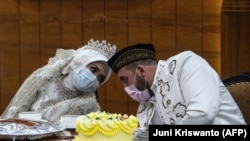 Pengantin perempuan Irra Chorina Octora asal Indonesia dan pengantin pria, Yavuz Ozdemir, dari Turki mengenakan masker di tengah kekhawatiran virus corona COVID-19, saat upacara pernikahan di Surabaya pada 25 Maret 2020.(Foto: Juni Kriswanto/AFP)