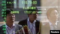 ພາບຂອງພວກຊາຍໜຸ່ມ ສະທ້ອນຈາກ ກະດານອີເລັກໂທນິກ ທີ່ສະແດງໃຫ້ເຫັນ ລາຄາສະເລ່ຍຂອງຮຸ້ນ ໃນຕະຫລາດຮຸ້ນ Nikkei ຂອງ ຍີ່ປຸ່ນ ແລະ ລາຄາ ການແລກປ່ຽນເງິນເຢນ ຂອງຍີ່ປຸ່ນ ກັບ ເງິນດອນລາຂອງສະຫະລັດຢູ່ທີ່ບໍລິສັດ ແຫ່ງນຶ່ງໃນນະຄອນຫລວງໂຕກຽວ, ວັນທີ 17 ພະຈິກ 2014.