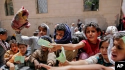 Yemenis present documents in order to receive food rations provided by a local charity, in Sanaa, Yemen. (File)