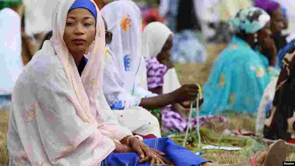 Muslim women sit in an open field before the start of prayers marking the end of Ramadan, in Lagos August 8, 2013.