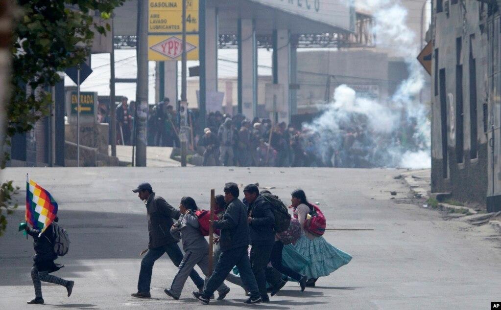 볼리비아 라파스에서 코카 재배 농민들과 진압 경찰이 맞서고 있는 가운데, 또다른 시위대가 길을 건너고 있다. 에보 모랄레스 볼리비아 대통령이 마취약이나 마약으로 유명한 코카인 성분이 함유된 코카 잎을 주변 국가로 수출하겠다고 지난달 밝힌 가운데, 정부는 합법적인 코카 재배면적을 2만㏊로 확대하는 계획을 발표했다. 동시에 불법 코카재배자를 최고 3년 징역형에 처할 수 있는 입법이 추진되면서 논란이 거세지는 중이다.