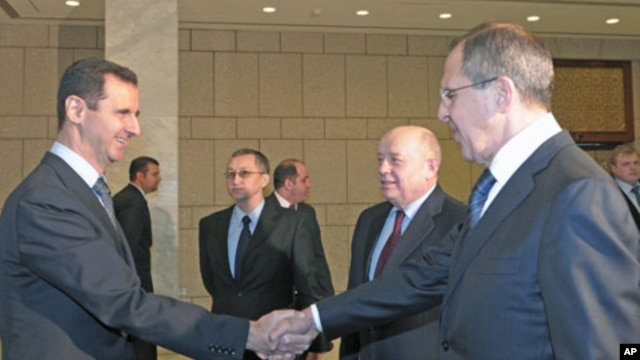 Syrian President Bashar al-Assad (L), shakes hands with Russian Foreign Minister Sergey Lavrov (R), as Russian Foreign Intelligence chief Mikhail Fradkov (2nd R) looks on during their meeting in Damascus, Syria, February 7, 2012.