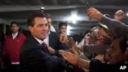 ທ່ານ Enrique Pena Nieto, ຜູ້ສະມັກເລືອກຕັ້ງປະທານາທິບໍດີເມັກຊິໂກ ຈາກພັກ PRI ຈັບມືກັບບັນດາຜູ້ສະໜັບ ສະໜຸນທ່ານ ຢູ່ສໍານັກງານໂຄສະນາຫາສຽງ ຂອງທ່ານ ທີ່ນະຄອນຫລວງ Mexico City, ໃນຕອນເຊົ້າວັນຈັນ ທີ 2 ກໍລະກົດ 2012. (AP Photo/Alexandre Meneghini)