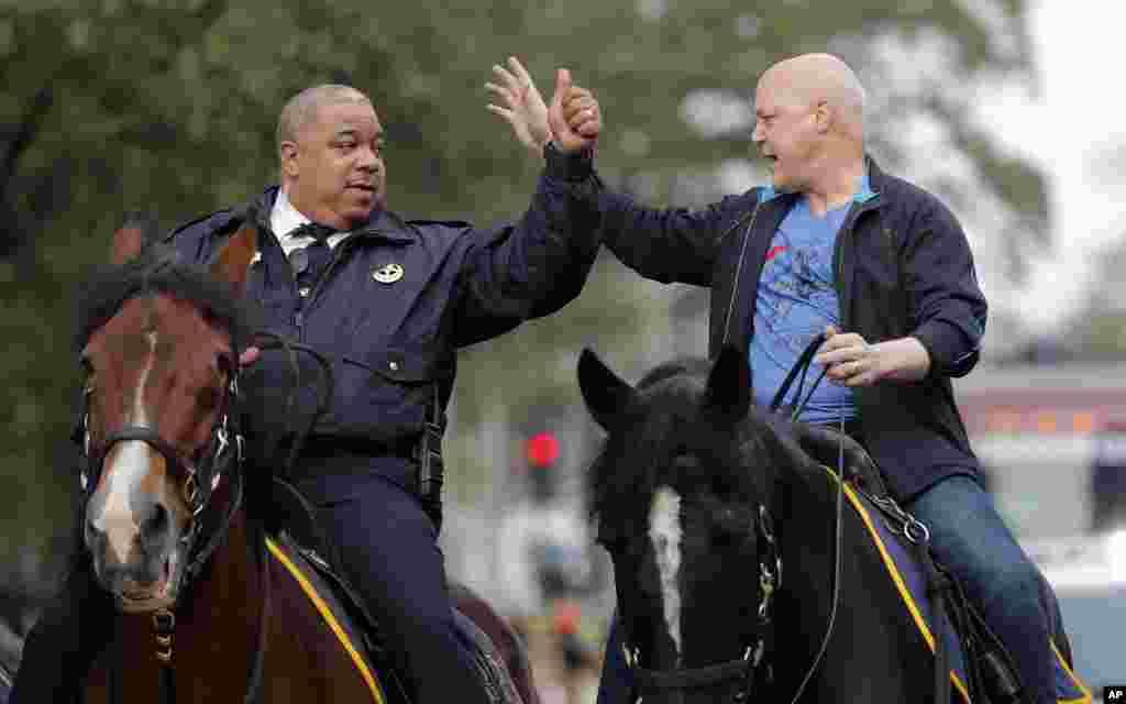 El alcalde de Nueva Orleáns, Mitch Landrieu, a la derecha, y el jefe de policía, Michael Harrison, cabalgan al comienzo del desfile de Krewe of Zulu el día del Mardi Gras, el martes 13 de febrero de 2018. (AP Photo / Gerald Herbert)
