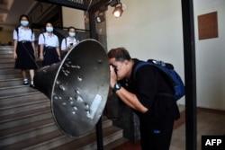 Seorang pria mengambil foto pengeras suara yang dilubangi peluru selama pembantaian Universitas Thammasat pada 6 Oktober 1976, pada pameran memperingati peristiwa di Universitas Thammasat di Bangkok pada 6 Oktober 2020. (Foto: AFP)