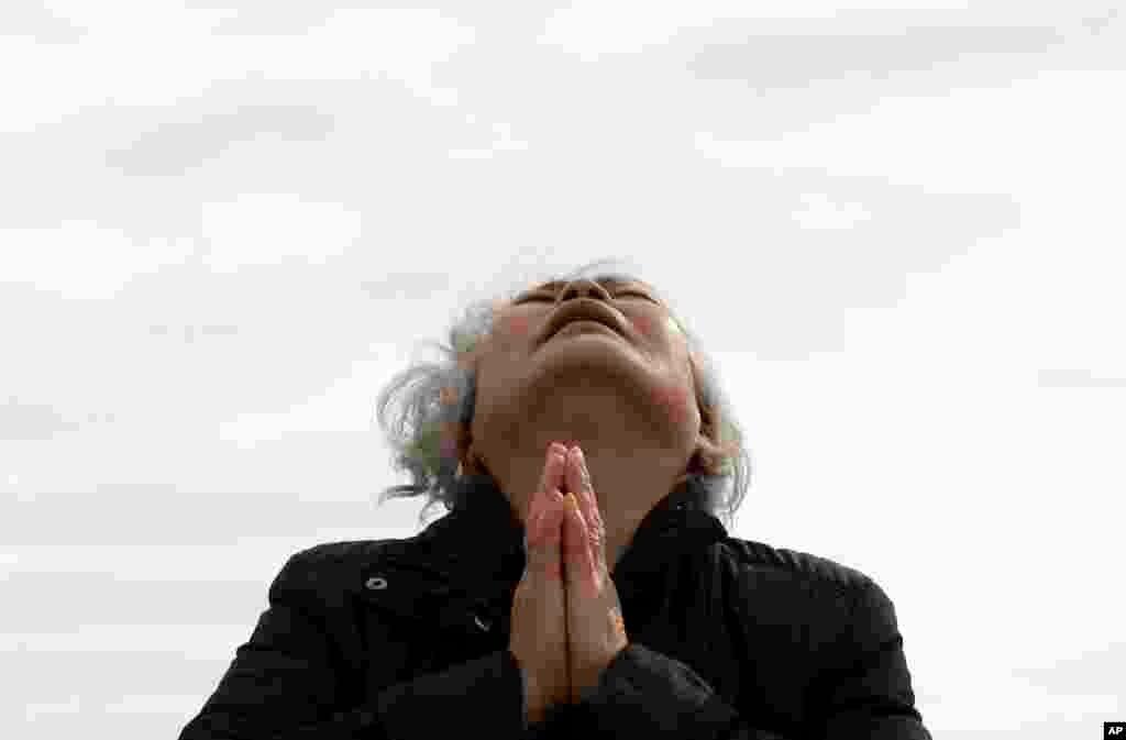 Thân nhân hành khách trên chiếc phà bị chìm vừa khóc vừa cầu nguyện trong lúc chờ đợi tin tức tại cảngJindo, Hàn Quốc, ngày 22/4/2014.