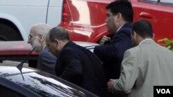 Alan Gross (izq.) cuando era llevado a juicio en marzo de 2011 por agentes de la seguridad cubana.