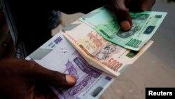 Un commerçant compte des billets de banque congolais à Kinshasa, RDC, 3 juillet 2012.