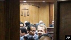Quelques personnes se tiennent dans la salle d'audiences au tribunal pénal du Caire, Egypte, 2 mars 2016.