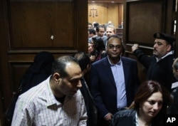 Investigative journalist Hossam Baghat, center, leaves a courtroom at the Cairo Criminal Court after the court postponed a decision on whether to implement an order to freeze his assets over allegations of illegal foreign funding, in Cairo, Egypt, March 24, 2016.