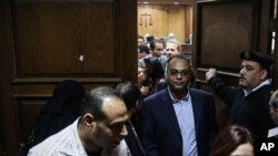 FILE - Investigative journalist Hossam Baghat, center, leaves a courtroom at the Cairo Criminal Court after the court postponed a decision on whether to implement an order to freeze his assets over allegations of illegal foreign funding, in Cairo, Egypt, March 2
