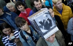 FILE - A protester wearing a hat depicting Russian President Vladimir Putin and reading 'Putin equals stagnation' is seen during a protest rally against a planned retirement age hike, in St. Petersburg, Russia, Sept. 16, 2018.