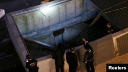 At least 14 concert-goers were killed in Seongnam, South Korea, when a ventilation shaft's grate on which they were standing collapsed. Police officials inspect the scene Oct. 17, 2014.