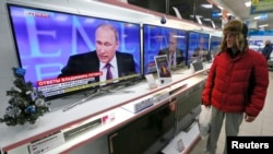 "FILE - A customer stands near TV sets during the annual end-of-year news conference of Russian President Vladimir Putin at the ""Pozitronika"" electronic store in Russia's Siberian town of Divnogorsk."