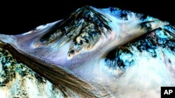 This undated photo provided by NASA and taken by an instrument aboard the agency's Mars Reconnaissance Orbiter shows dark, narrow, 100 meter-long streaks on the surface of Mars that scientists believe were caused by flowing streams of salty water. (NASA/J