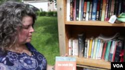 언론인 캣 라자로프 씨가 '리틀 프리 라이브러리(Little Free Library)'에서 책을 꺼내들고 있다.