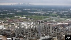 FILE - The TPC petrochemical plant is shown with downtown Houston in the background, Aug. 29, 2017.