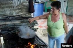 Margarita Rojas cooks the meal using firewood at her house in San Cristobal, Venezuela, Aug. 5, 2017.