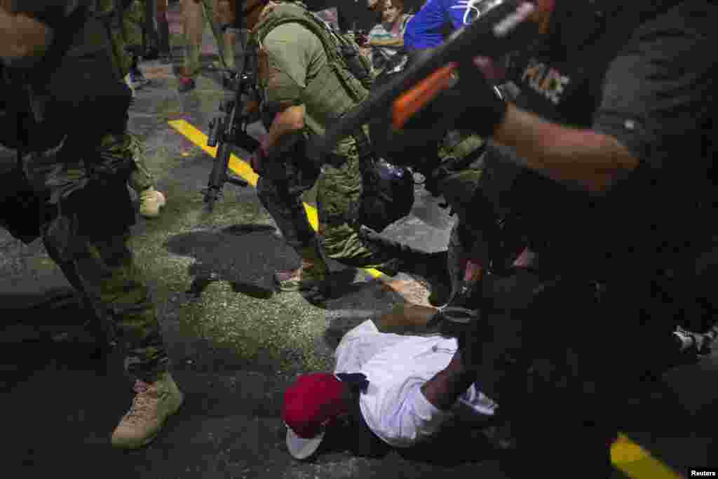 Security forces detain a demonstrator during a protest against the shooting of unarmed black teen Michael Brown, in Ferguson, Missouri, Aug. 20, 2014.