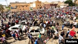 People gather at the scene of a car bomb explosion outside a hospital in Benghazi, Libya, May 13, 2013.