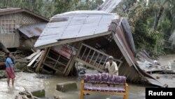 Warga membersihkan sofa di luar rumah mereka yang hancur dihantam topan Bopha di Lembah Compostela, FIlipina Selatan (5/12).