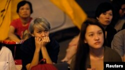 争取民主的示威者在香港政府总部附近的视频屏幕上观看抗议活动领袖和政府官员的对话。