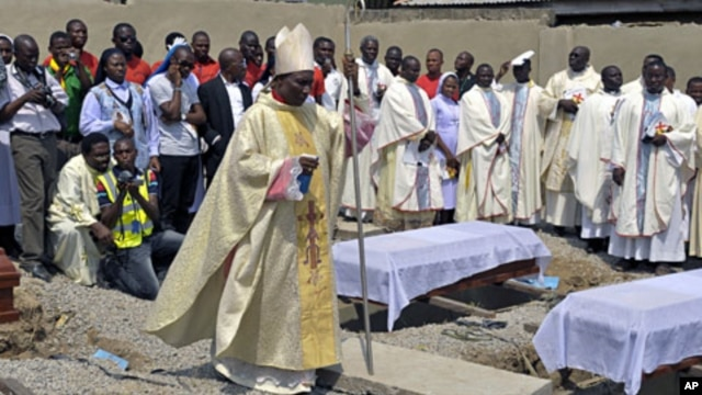 Clergymen gather around the coffins of the victims of the Christmas day bombing at St Theresa Catholic Church Madalla, during a mass funeral for the victims, outside Nigeria's capital Abuja, February 1, 2012