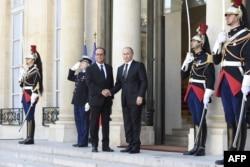 ປະທານາທິບໍດີຝຣັ່ງ ທ່ານ Francois Hollande (ຊ້າຍ) ຈັບມືກັບ ປະທານາທິບໍດີຣັດເຊຍ ທ່ານ Vladimir Putin
