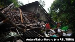 Seorang pria menyelamatkan barang miliknya di sebuah rumah yang rusak akibat gempa bumi di Lumajang, Jawa Timur, 11 April 2021. (Foto: Antara/Zabur Karuru via REUTERS)