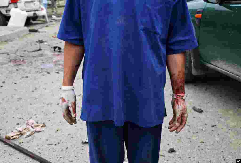 An Afghan health worker stands after a suicide attack that struck the convoy of presidential candidate Abdullah Abdullah in Kabul, June 6, 2014.