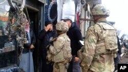 Pasukan AS yang berbasis di sekitar kota Manbij di Suriah berbicara dengan penduduk, di Suriah utara, Minggu, 23 Desember 2018. (Facebook Dewan Militer Kota Manbij via AP).