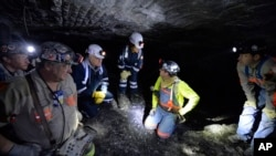 FILE - In this Jan. 13, 2015 file photo, Joe Main, third from left, Assistant Secretary of Labor for Mine Safety and Health, and Patricia Silvey, center, Deputy Assistant Secretary for Operations with MSHA, speak with workers at the Gibson North mine, in Princeton, Indiana.