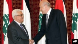 Outgoing Lebanese Prime Minister Najib Mikati, right, shakes hands with Palestinian President Mahmoud Abbas, left, at the government house, in Beirut, Lebanon, July 4, 2013.