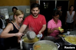 Diego Prada (C), Maria Luisa Pombo (L) and other volunteers of the Make The Difference (Haz La Diferencia) charity initiative prepare soup to be donated, at Maria Luisa's kitchen in Caracas, March12, 2017.