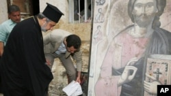 In this photo taken on Sunday, April 20, 2014 and released by the Syrian official news agency SANA, Syrian President Bashar Assad, center, removes a book from the ground next to a religious icon during his visit to the Christian village of Maaloula, near Damascus, Syria. (AP Photo/SANA)