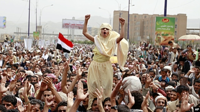 A girl stands above the crowd as anti-government protesters shout slogans during a rally to demand the ouster of Yemen's President Ali Abdullah Saleh on the first Friday of the month of Ramadan in Sana'a, August 5, 2011