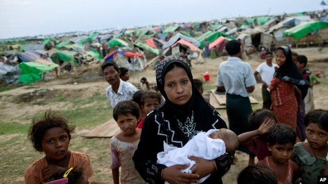 FILE - An internally displaced Rohingya woman holds her newborn baby surrounded by children in the foreground of makeshift tents at a camp for Rohingya people in Sittwe, northwestern Rakhine State, Burma.