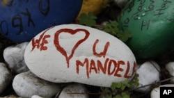 """Uma pedra pintada com as palavras """"Nós amamos-te Mandela'"""