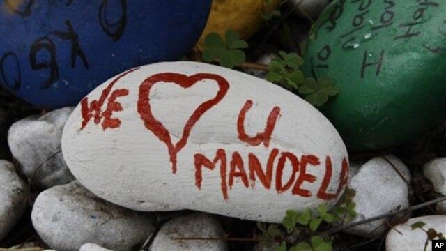 Sebuah batu bertuliskan 'Kami Mencintaimu Mandela' yang diperuntukkan bagi mantan presiden Nelson Mandela diletakkan di depan rumahnya di Houshton, pinggiran Johannesburg, di mana ia beristirahat setelah keluar dari rumah sakit (foto, 27/12/2012).