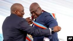 ប្រធានាធិបតីកុងហ្គោ Felix Tshisekedi (ស្ដាំ) ទទួលខ្សែតំណាងប្រធានាធិបតីពីអតីតប្រធានាធិបតីដែលចេញពីតំណែង លោក Joseph Kabila ក្រោយពេលស្បថចូលកាន់តំណែងនៅទីក្រុងគីនស្ហាសា សាធារណរដ្ឋប្រជាធិបតេយ្យកុងហ្គោ កាលពីខែមករា ២០១៩។