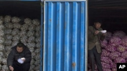 中国10月通胀率创25个月新高。在北京的一个蔬菜批发市场,蒜农一边吃午饭