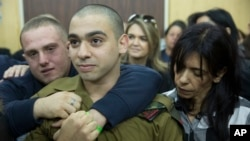 FILE - Israeli solider Sgt. Elor Azaria waits with his parents for the verdict inside the military court in Tel Aviv, Israel on Jan. 4, 2017.