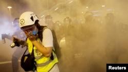 在香港警察向反送中示威者發射催淚彈後一名記者用手掩住口鼻。 (2019年8月4日)