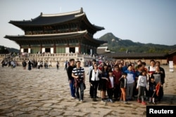 FILE - Chinese tourists pose for a group photo at the Gyeongbok Palace in central Seoul, South Korea, Oct. 5, 2016. About 8 million Chinese tourists have visited South Korea in the last five years.