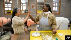 Poor Clares nuns Sister Maria Eden, left, and Sister Thereza share a laugh as they make altar bread also known as communion wafers, Sept. 8, 2015, at the Monastery of Saint Clare in Langhorne, Pa.