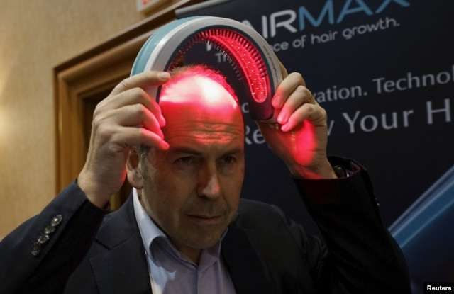 FILE - BBC television reporter Rory Cellan-Jones tries out a HairMax Laserband, a hands-free device described to treat hair loss and cause new hair growth, during the opening event at the Consumer Electronics Show in Las Vegas, Jan. 4, 2016.